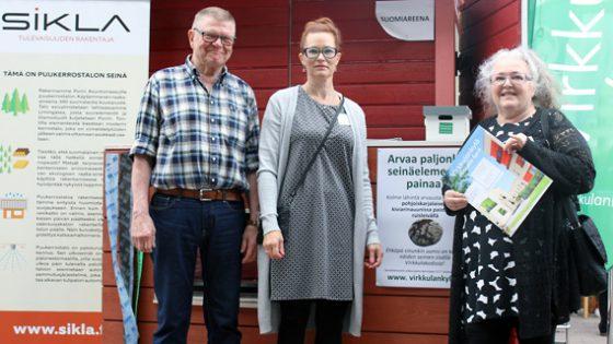 Porin SuomiAreenassa kesällä 2017 arvuuteltiin puurakenteisen seinäelementin painoa. Tapahtumavieraita opastivat Kuusikkoahon osastolla Leo Tolonen, Tuija Nenonen ja Helinä Kalaja.